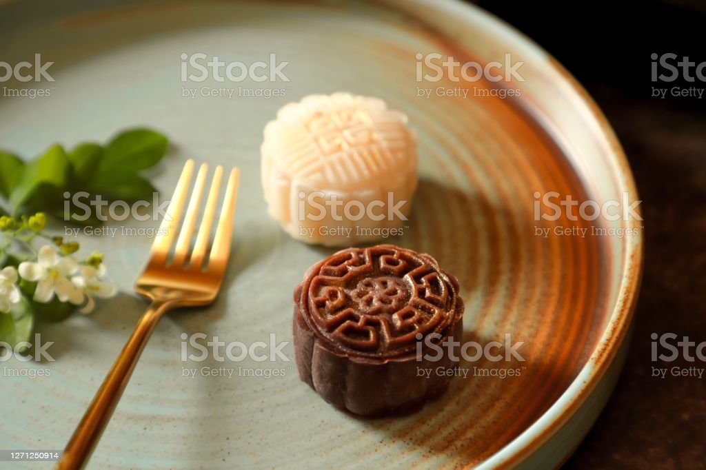 Snowskin Mooncake, the non-traditional mooncake that doesn't require any baking. Sweet bean paste wrapped in mochi dough of various flavours, then moulded in mooncake mould. Two mooncakes of cocoa and milk flavours are arranged on a artistic ceramic plate; focus is on the cocoa mooncake. Orange Jasmine bouquet are used as decoration. A golden fork is placed on the plate between the mooncakes and the bouquet.